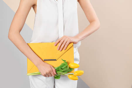 Stylish woman with clutch and spring flowers against color background, closeup