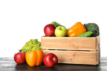 Wooden crate filled with fresh vegetables and apples on table against white background Banco de Imagens