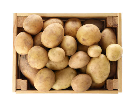 Wooden crate full of fresh raw potatoes on white background, top view