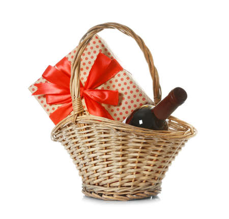 Basket with bottle of wine and gift on white background