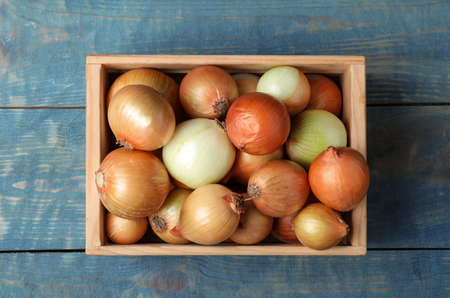 Crate full of fresh onion bulbs on wooden background, top view 写真素材