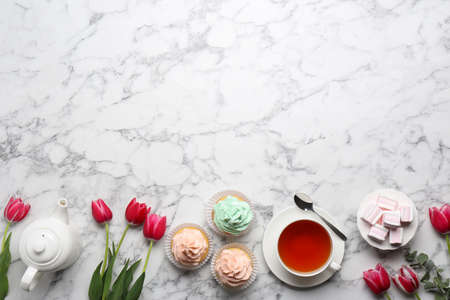 Beautiful composition with tea, desserts and tulips on marble background, flat lay. Space for text