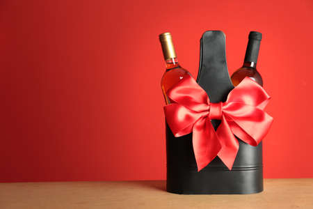 Bottles of wine in holder with bow on table against color background. Space for text 版權商用圖片