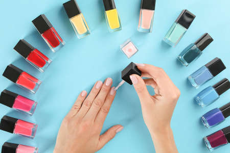 Woman applying nail polish on color background, above view