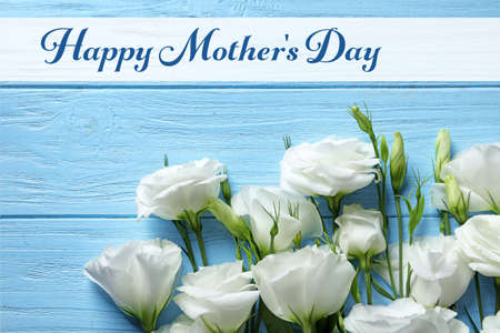 Beautiful eustoma flowers and text Happy Mothers Day on wooden background, top view Imagens