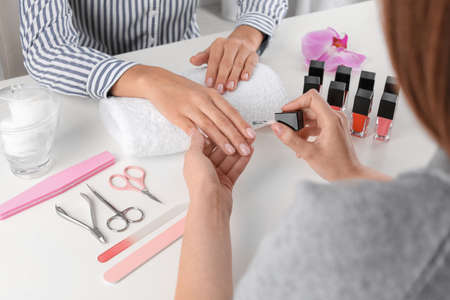 Manicurist painting clients nails with polish in salon, closeup