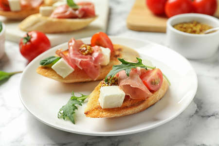 Plate of tasty bruschettas with prosciutto on table Фото со стока
