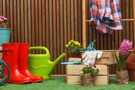 Composition with different gardening tools on artificial grass at wooden wall Standard-Bild
