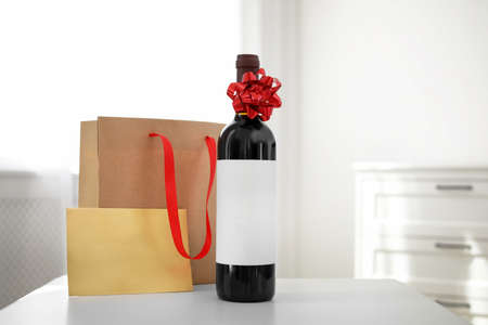 Bottle of wine, card and paper bag on table in light room. Space for text