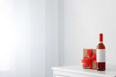 Bottle of wine and gift box on table in light room. Space for text Stok Fotoğraf - 124989433