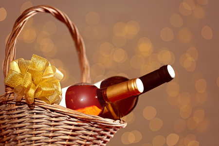 Bottles of wine in wicker basket with bow against blurred lights
