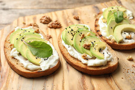 Delicious bruschettas with avocado served on wooden board, closeup