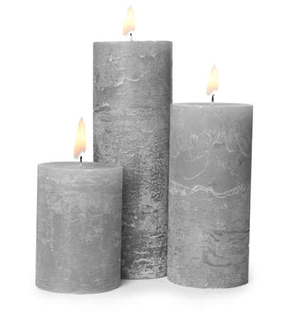 Three alight wax candles on white background
