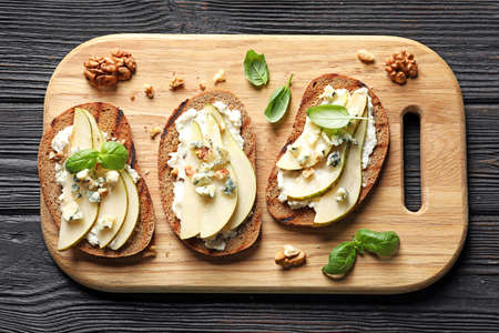 Delicious bruschettas with pear served on wooden table, flat lay