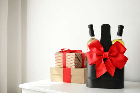 Bottles of wine in holder with bow and gift boxes on table in light room. Space for text Stok Fotoğraf