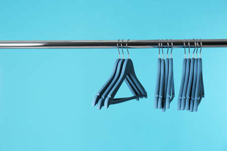Metal rack with clothes hangers on color background, space for text Banco de Imagens