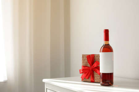 Bottle of wine and gift box on table in light room. Space for text Stok Fotoğraf - 124990182
