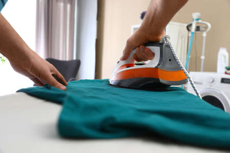 Man ironing clothes on board at home, closeup Banco de Imagens