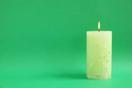 Alight wax candle on color background. Space for text