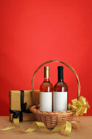 Bottles of wine in wicker basket with bow and gift on table against color background. Space for text Stok Fotoğraf