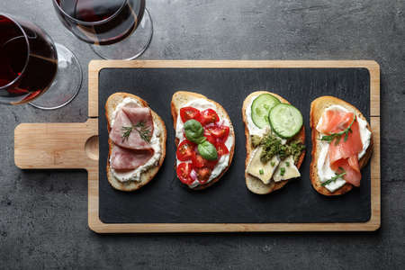 Different tasty bruschettas served with wine on grey table, flat lay