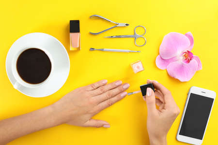 Woman applying nail polish on color background, top view Imagens - 124992134