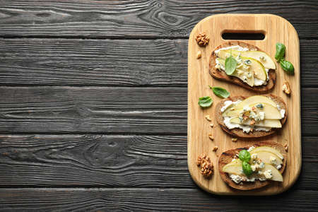 Wooden board with delicious pear bruschettas on table, flat lay. Space for text