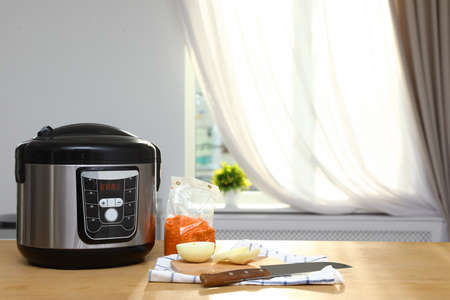 New modern multi cooker and products on table in kitchen. Space for text 写真素材 - 124992299