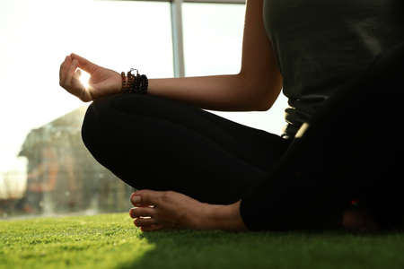 Young woman practicing yoga in sunlit room, closeup Stock Photo