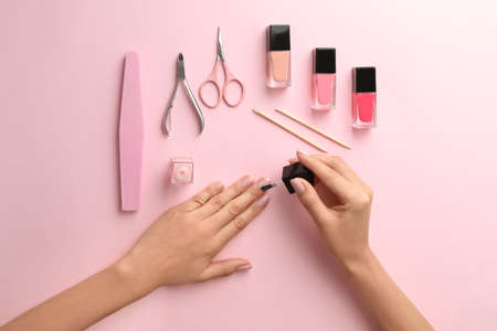 Woman applying nail polish on color background, top view