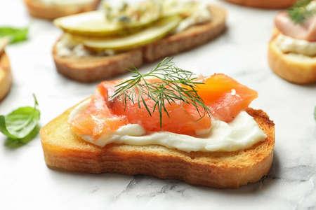 Tasty bruschetta with salmon on marble table
