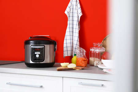 New modern multi cooker and products on table in kitchen 写真素材 - 124992315