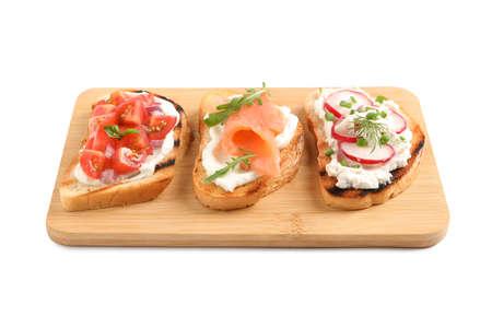 Board with different tasty bruschettas on white background Banco de Imagens