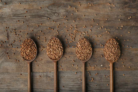 Spoons with uncooked buckwheat on wooden table, flat lay. Space for text Imagens - 124992335