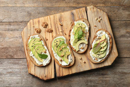 Board with avocado bruschettas on wooden table, flat lay