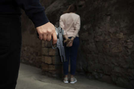 Armed man holding woman hostage outdoors, focus on hand with gun. Criminal offence Banco de Imagens