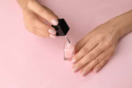Woman applying nail polish on color background, closeup