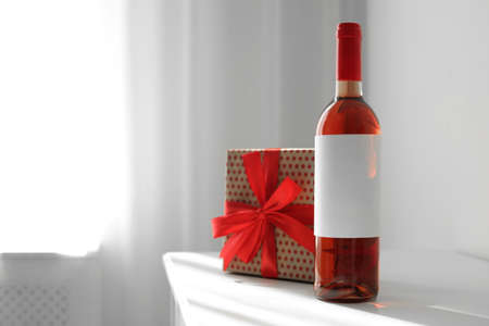 Bottle of wine and gift box on table in light room. Space for text Imagens - 124992354