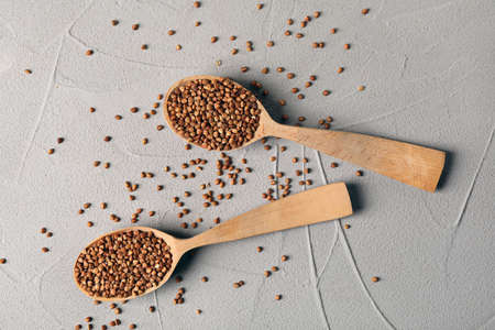 Wooden spoons with uncooked buckwheat on grey background, flat lay