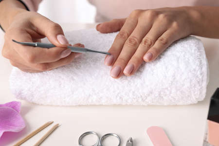 Woman preparing fingernail cuticles at table, closeup. At-home manicure 版權商用圖片