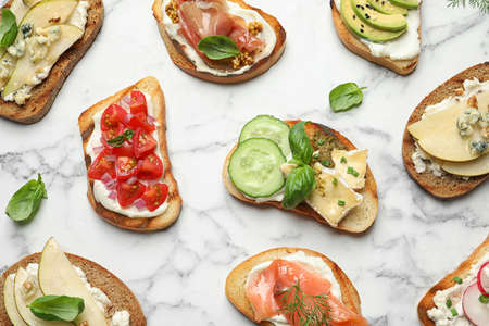 Different tasty bruschettas on marble background, flat lay