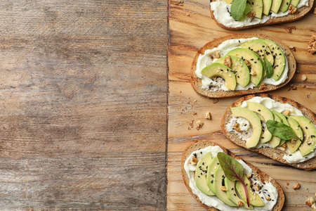 Board with avocado bruschettas on wooden table, flat lay. Space for text