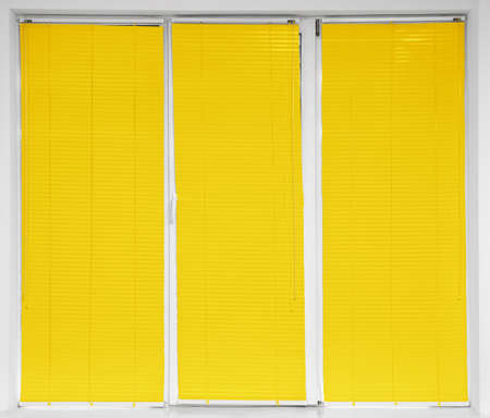 Modern window with closed stylish yellow blinds