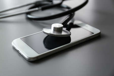 Smartphone and stethoscope on grey table, closeup. Repairing service