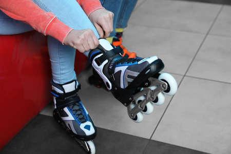 Woman putting on roller skates indoors, closeup Stock Photo