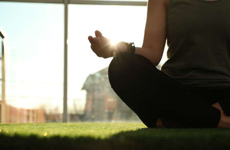 Young woman practicing yoga in sunlit room, closeup with space for text Stock Photo