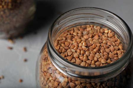 Uncooked buckwheat in glass jar on table, closeup Banco de Imagens - 124992649
