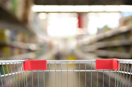 Blurred view of supermarket and empty shopping basket, closeup Banco de Imagens