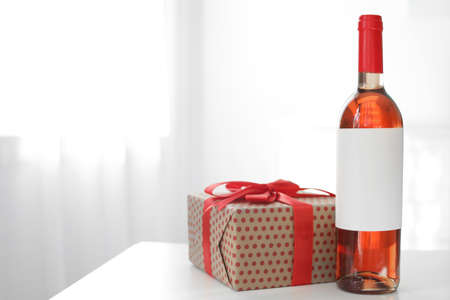 Bottle of wine and gift box on table in light room. Space for text