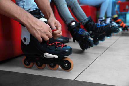 Man putting on roller skates indoors, closeup